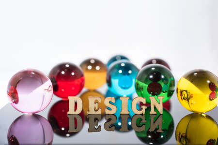 Abstract composition with transparent glass balls and wooden letters.
