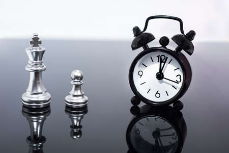 Chess pieces and alarm clock, the passage of time and accumulation Stockfoto