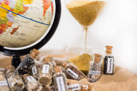 Glass test-tube with sand of different summer vacation countries. Located in sand with small globe and Hourglass