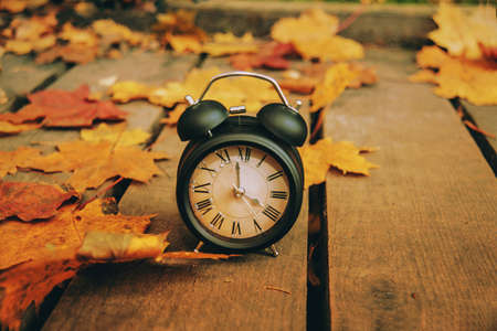 Retro styled photo. Vintage black alarm clock on autumn leaves. Time change abstract photo. Daylight saving time.