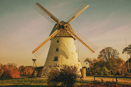 Restored old windmill on the mountainside. Autumn sunny day. Retro styled photo. Stock Photo