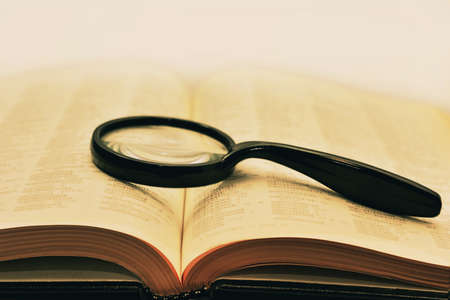 Retro styled photo. Old books with magnifying glass. Isolated documents on white background.