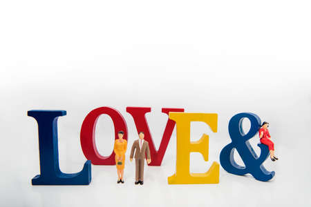 Love triangle. Abstract photo of love and lovers. Big wooden letters with small plastic people figures.
