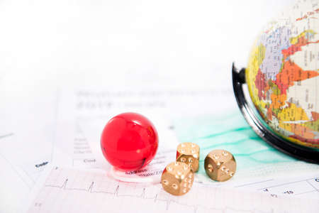 Medicine documents with golden game dices and small globe on it. Abstract photo of illness time.
