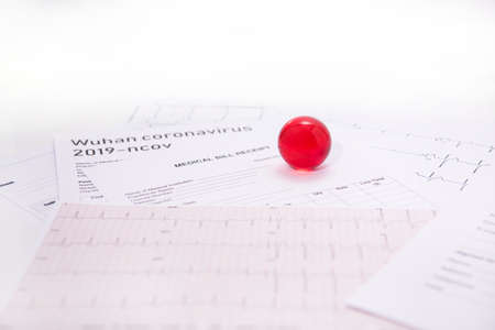 Medicine documents with small red glass balls on it. Abstract photo of illness time.