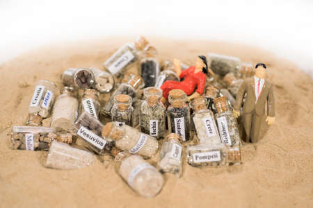 Glass test-tube with sand of different summer vacation destinations. Vacation time abstract photo.
