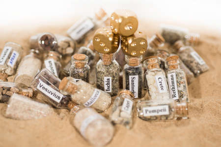 Glass test-tube with sand of different summer vacation countries and game dice