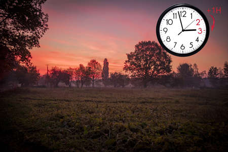 Daylight Saving Time (DST). Blue sky with white clouds and clock. Turn time forward (+1h). Stock Photo