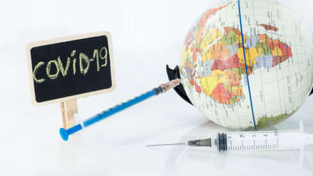 Small globe with  syringe in it. Abstract illness concept.