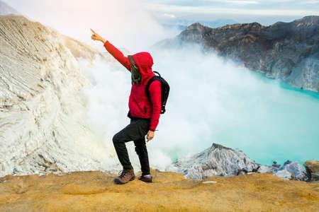crater lake: man on top of kawa ijen mountain indonesia. Stock Photo