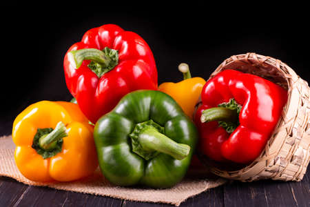 Three sweet peppers on a wooden background, Cooking vegetable salad Stock Photo