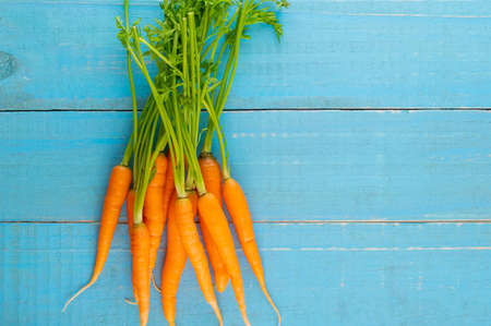Fresh and sweet carrot on a grey wooden table