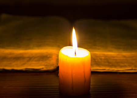 Yellow candle light with the holy bible in dark background Stock Photo - 65100407