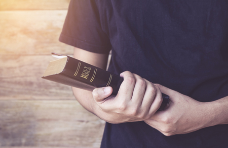 man holding holy bible in hands with wooden background, Copy space Stock Photo