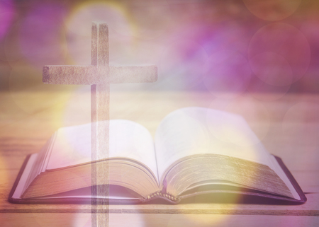 soft focus of bible with wooden cross on wooden table, vintage tone with light bokeh effected Stock Photo