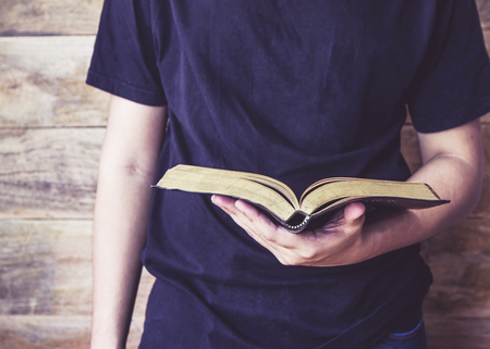 a young man in black t-shirt holding holy bible over wooden background