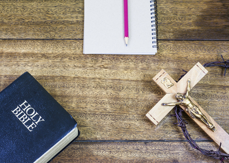 image of the crucifix , holy bible and small note book with red pencil on wooden background for christian background with copy space, concept Stock Photo