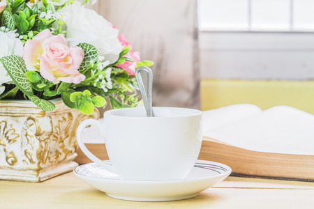 image of a cup of coffee with opened bible and flower on wooden table