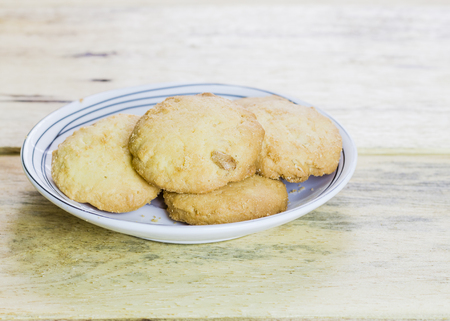 brown cookies in white dish on wooden background Stock Photo