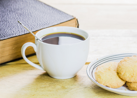 image of the old book with a cup of coffee and cookies on wooden background, vintage tone light effect