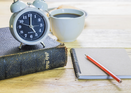 image of the old book with alarm clock, small note book, pencil and a cup of coffee on wooden background, vintage tone light effect