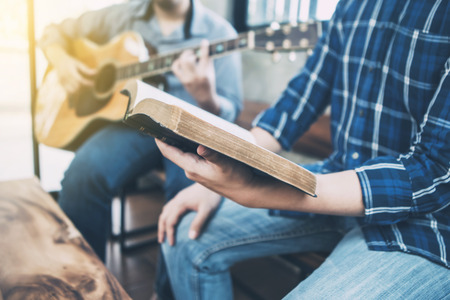a man sing a song from hymn book while his friends playing guitar indoor Stock Photo