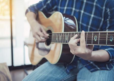 close up of a a man playing guitar indoor