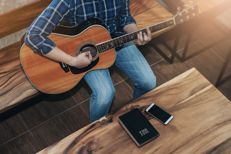 close up of a a man playing guitar with bible and smart phone on wooden table, praise and worship concept Stock Photo