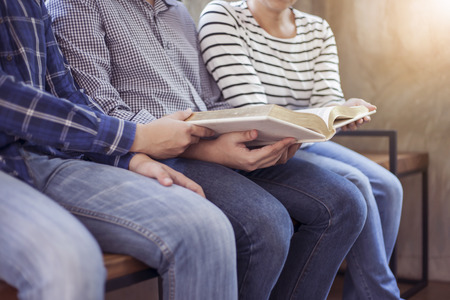 Christian friends group reading and study bible together in home