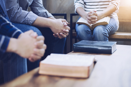 group of christian  sitting around wooden table with open blurred bible page and praying to God together