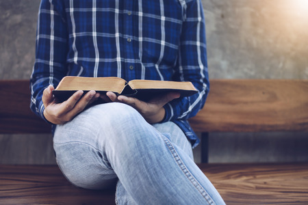 Close up of a man sit  on wooden chair  holding holy and read bible  with window light