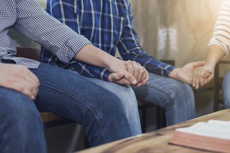 Three christian people holding hands and pray together with bible on wooden table Stock Photo