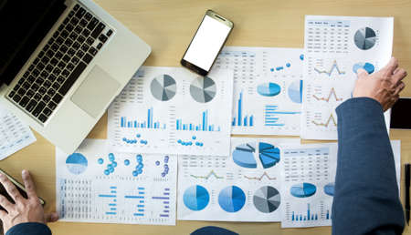 businessman hands working with computer and smart phone with business graph on desk as concept.