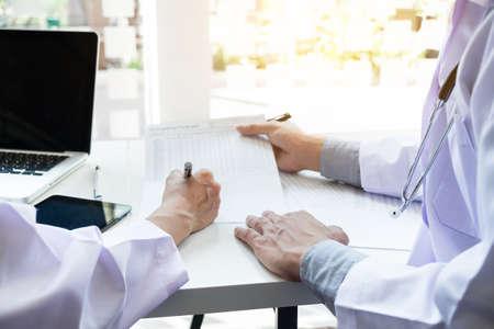 Dois doutores que discutem a história paciente em um escritório que aponta a uma prancheta com papel do original como fazem um diagnóstico ou recomendam no tratamento. Foto de archivo