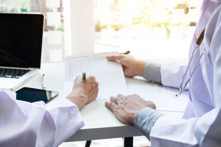 Two doctors being discussing patient history in an office pointing to a clipboard with document paper as they make a diagnosis or recommend on treatment. Stock Photo