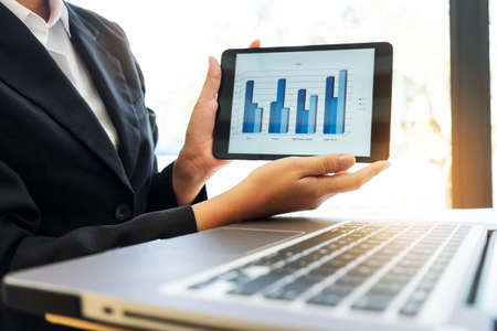 Close-up of businesswoman showing and presenting for financial graph on digital tablet and computer labtop at workplace in office.