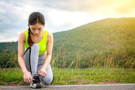 Shot of young woman runner tightening running shoe laces, getting ready for jogging exercise outdoors. Female jogger lacing her sneakers standing on road path before morning run.