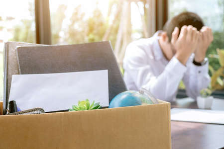 Images of packing up all his personal belongings and files into a brown cardboard box and Businessman  has stress to resignation, resign concept.