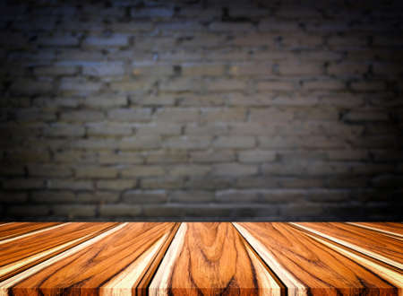Selected focus empty brown wooden table and wall texture or old black brick wall blur background image. for your photomontage or product display.