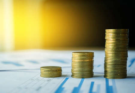 Money and financial concept, stack of coin on many business document graph with sunlight in the morning.