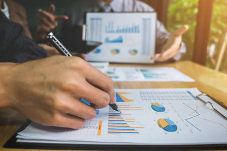 co: Co working conference, Business team meeting present, investor colleagues discussing new plan financial graph data on office table with laptop and digital tablet, Finance, accounting, investment. Stock Photo