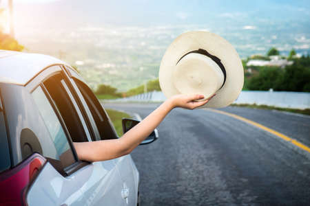 Relaxed happy traveler, Young beatiful asian gilr holding hat weave and Reach out of the car at sunset and beautiful view with mountain road background.
