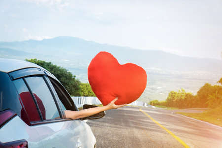 Relaxed happy traveler, Young beatiful asian gilr holding big red heart and Reach out of the car at sunset and beautiful view with mountain road background.