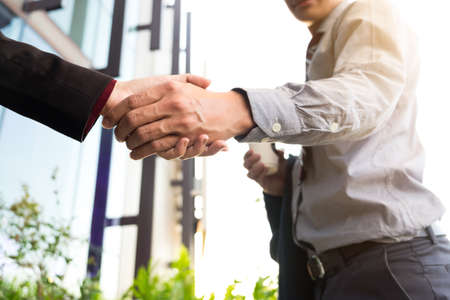 Happy smiling business man shaking hands after a deal finishing up a meeting, business outdoors concept. Stock Photo