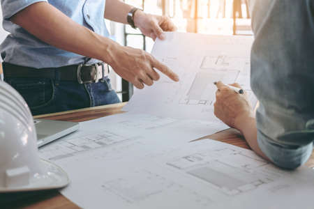 Image of engineer or architectural project, Close up of Architects engineer's hands drawing plan on BluePrint and discussing to partner with Engineering tools on workplace, Construction concept .