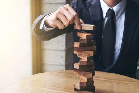 Concept de risque alternatif, plan et stratégie dans les entreprises, Risque de créer un concept de croissance Buiness avec des blocs en bois, Images de la main des hommes d'affaires qui placent et tirent un bloc de bois sur la tour.