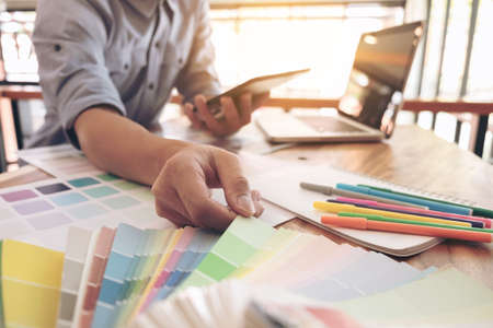Color samples, color swatch samples, Draw architecture, Graphic designer selecting on colour chart, pens at workplace, Working with laptop and tablet on wooden desk. Archivio Fotografico