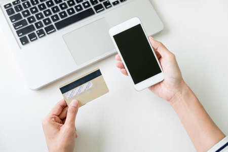 money packs: Happy Woman using smart phone and credit card register payments online shopping and customer service network connection market, using technology on laptop, Internet Online shopping or banking concept. Stock Photo