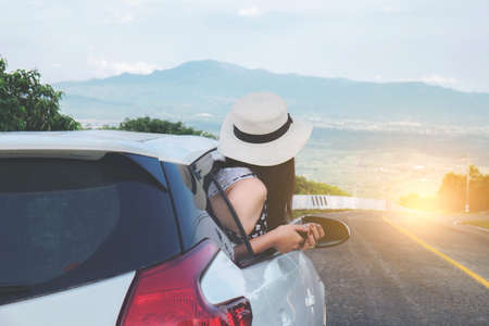 Relaxed happy traveler, Young beatiful asian gilr wearing white Hat weave using smart phone and Reach out of the car at sunset and beautiful view with mountain road background.