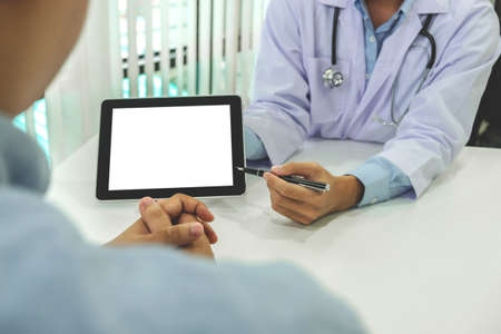 Doctor consulting patient and recommend treatment methods and how to rehabilitate the body, presenting results on tablet computer in hospital office